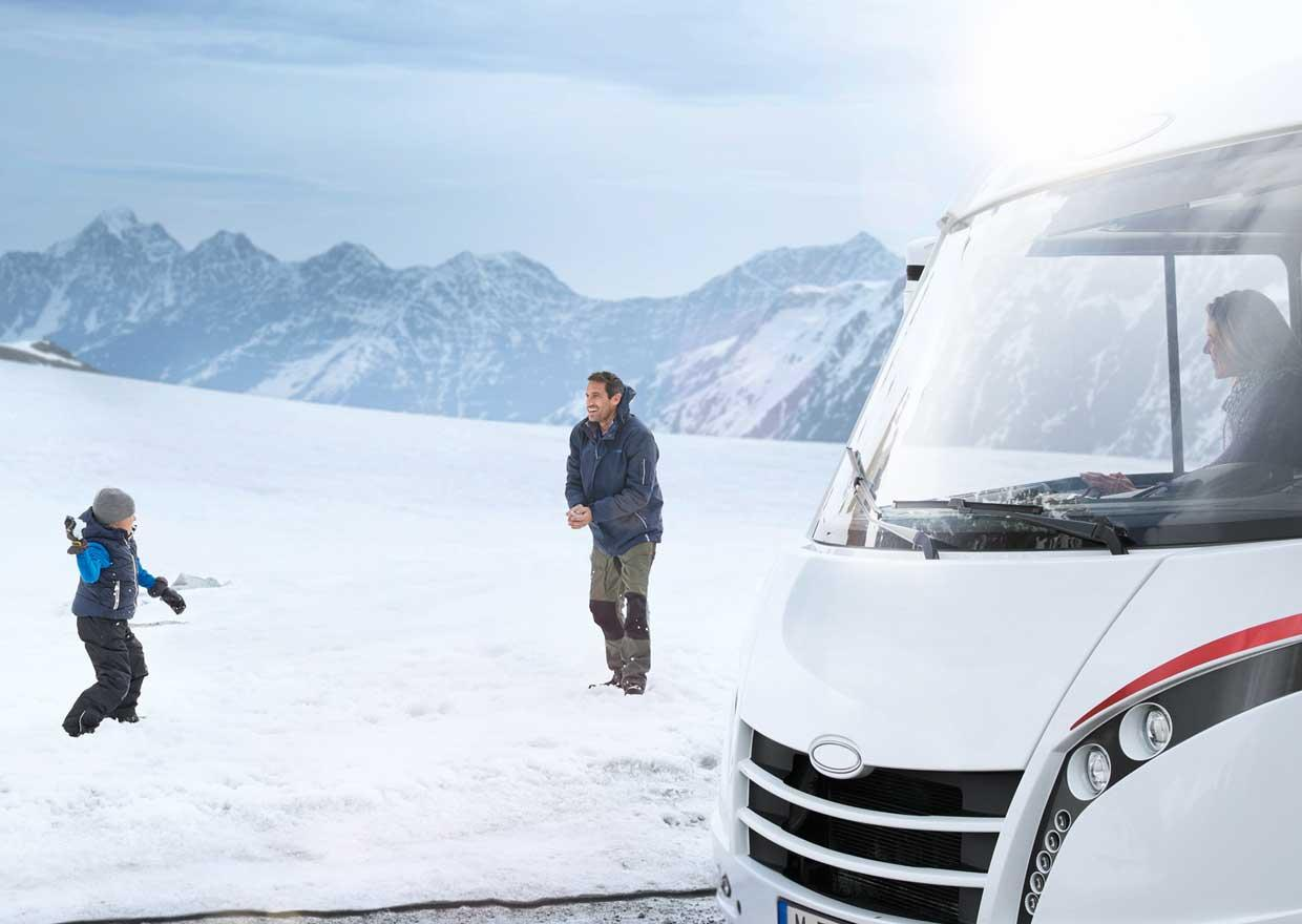 Father and son having a snowball fight in front of a motor caravan