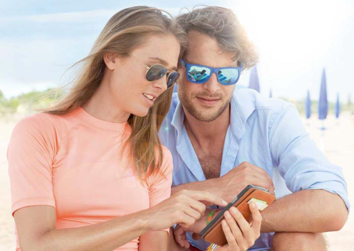 Couple sitting in the sun and looking at a smartphone
