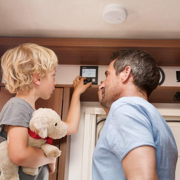 Father and his son inside a caravan using the digital control panel CP plus