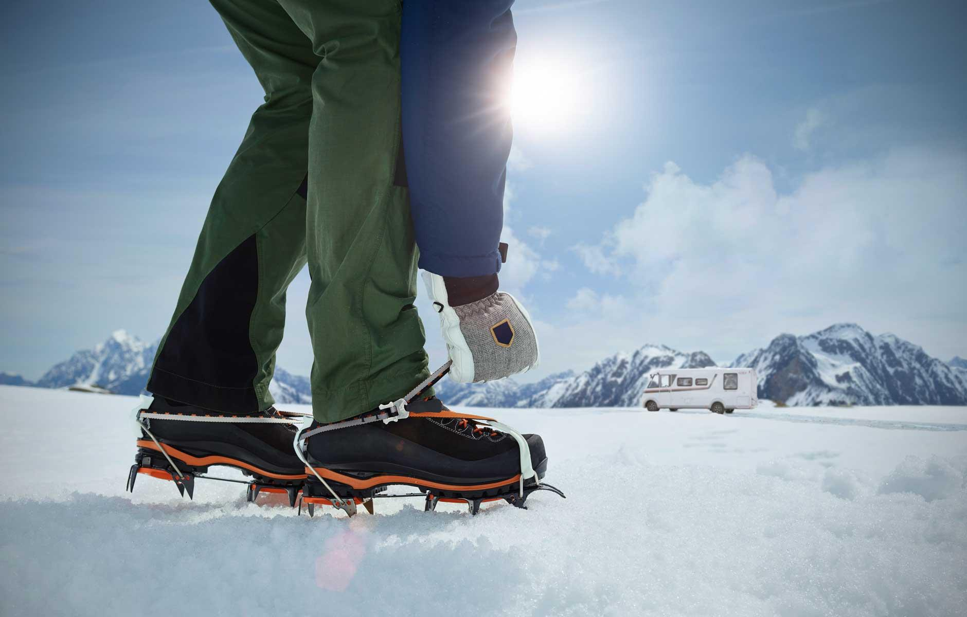 Man with crampons on snow in front of motorcaravan