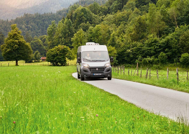 Motor caravan on a small street in a mountain landscape
