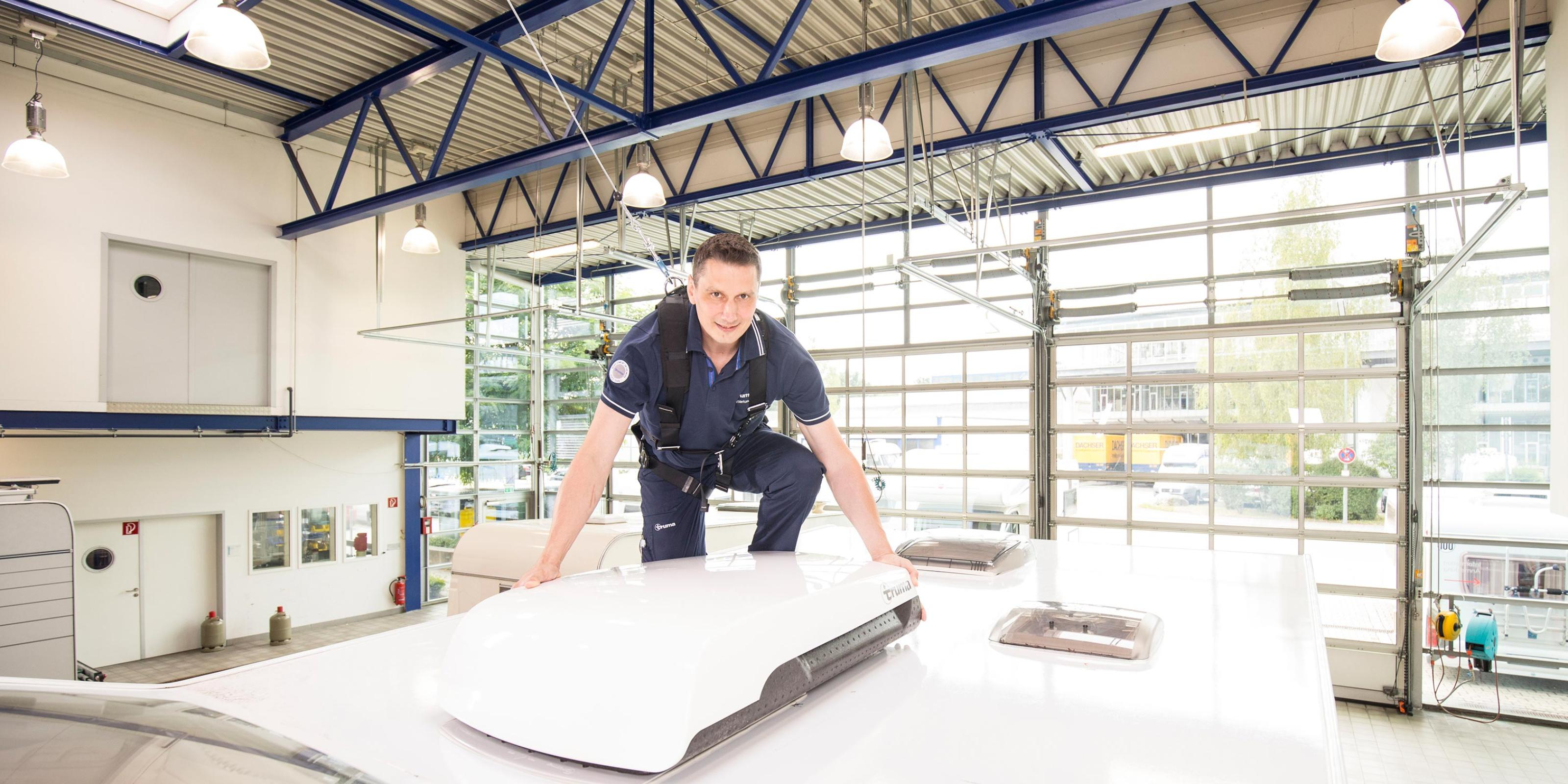 Truma employee installating a Truma Aventa roof-mounted air-conditioning system in the Truma service workshop