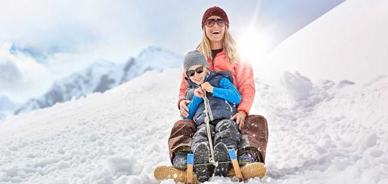 Mother and son sitting on a sledge in the snow