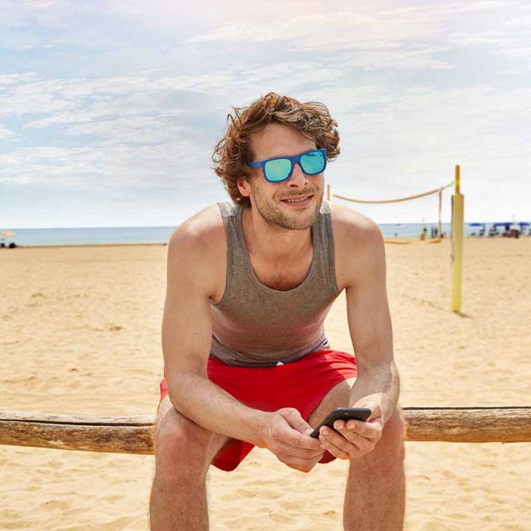 Man with smartphone sitting on a bench on the beach
