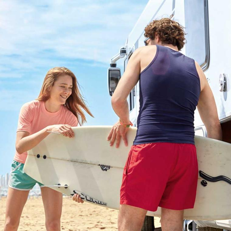 Young couple taking a surfboard out of their motorcaravan.