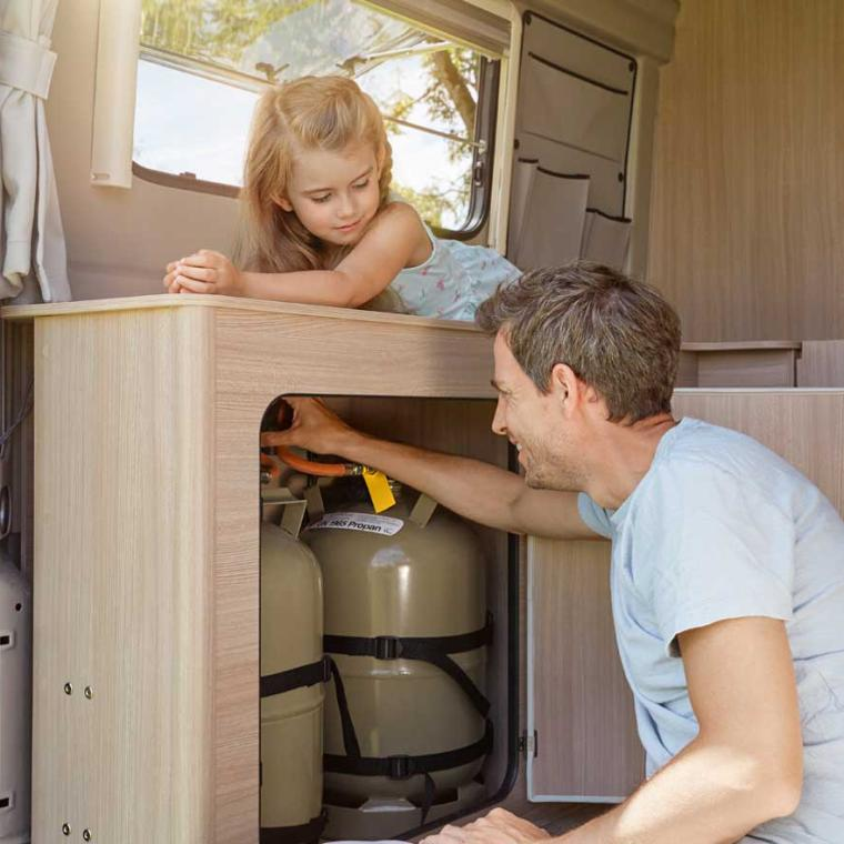 Little girl watches her father putting the gas cylinder on in the gas locker