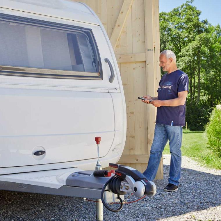 Man moving a caravan with a mover into a garage