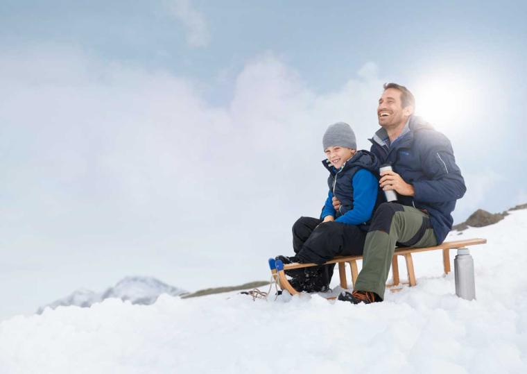 Father and son sitting on a sledge in the snow