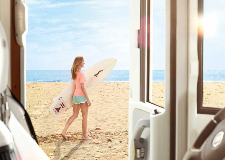 Woman with surfboard in front of motor caravan