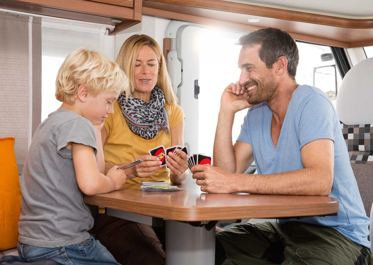 Family playing cards in a motor caravan