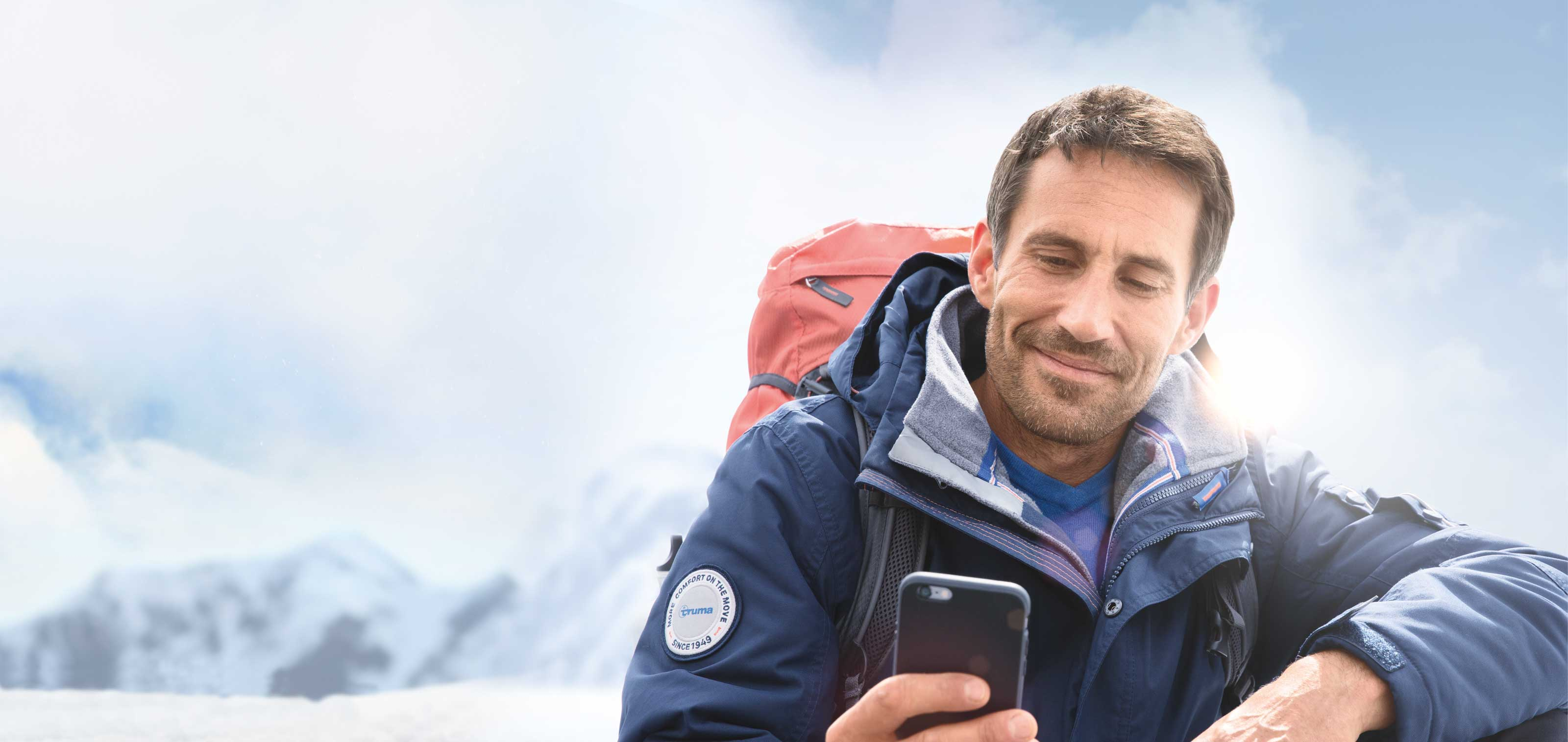 Man with backpack and outdoor jacket looking at the smartphone