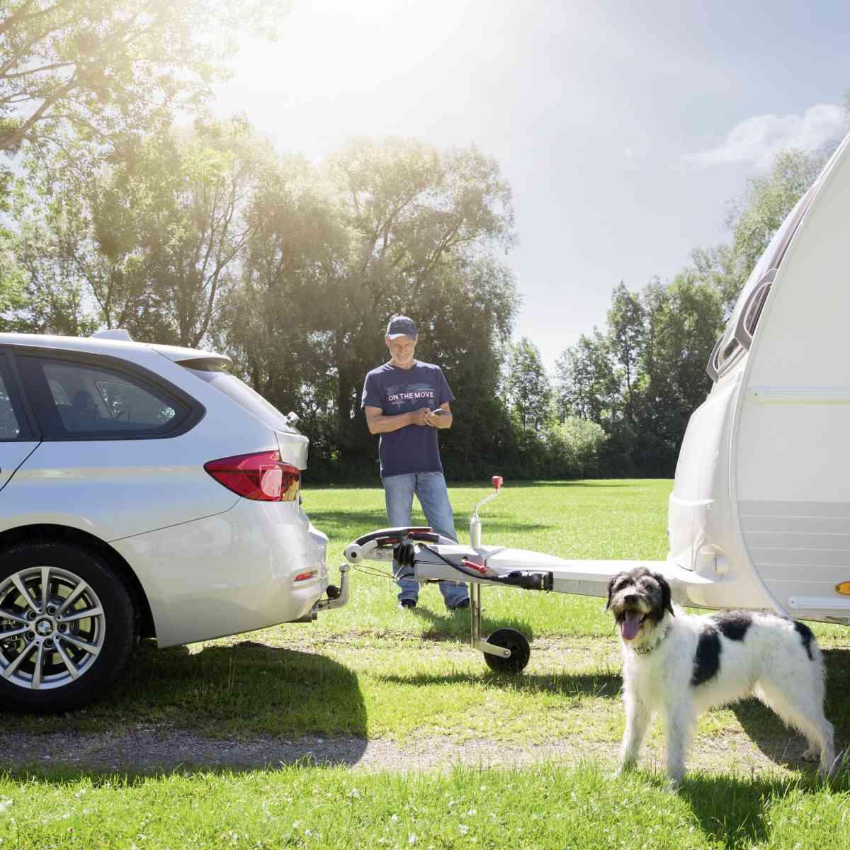 Man couples caravan with a mover on a car