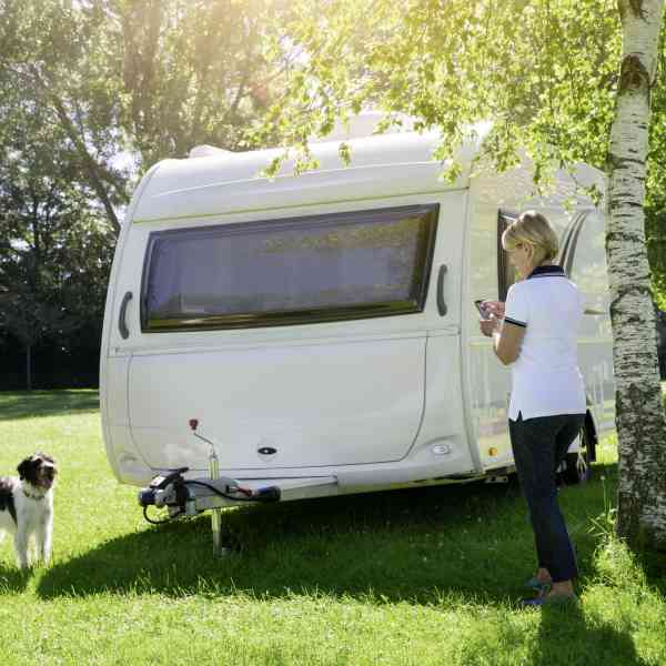 Woman with a dog moving a caravan