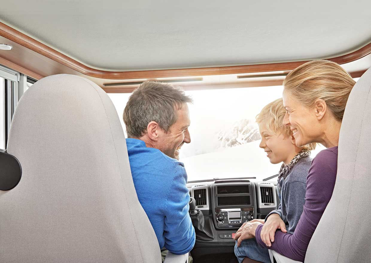 View to a family in the drivers cab of a motor caravan