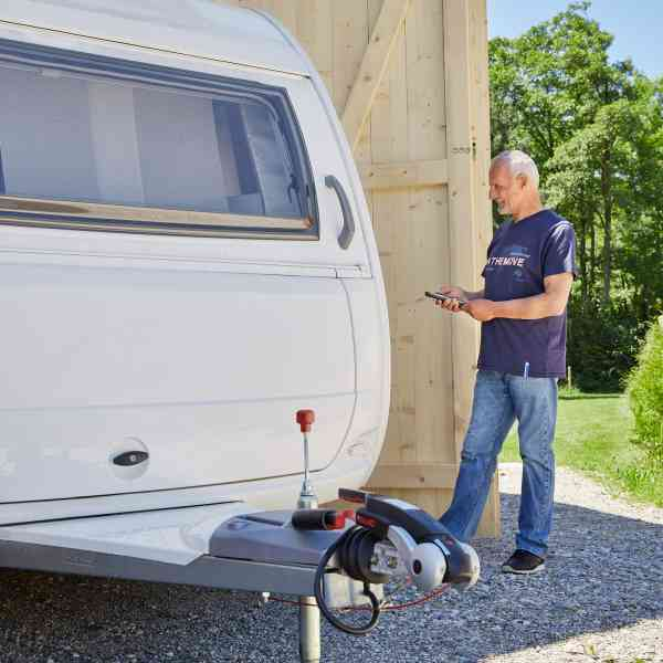 Man moving a caravan with a mover into a garage