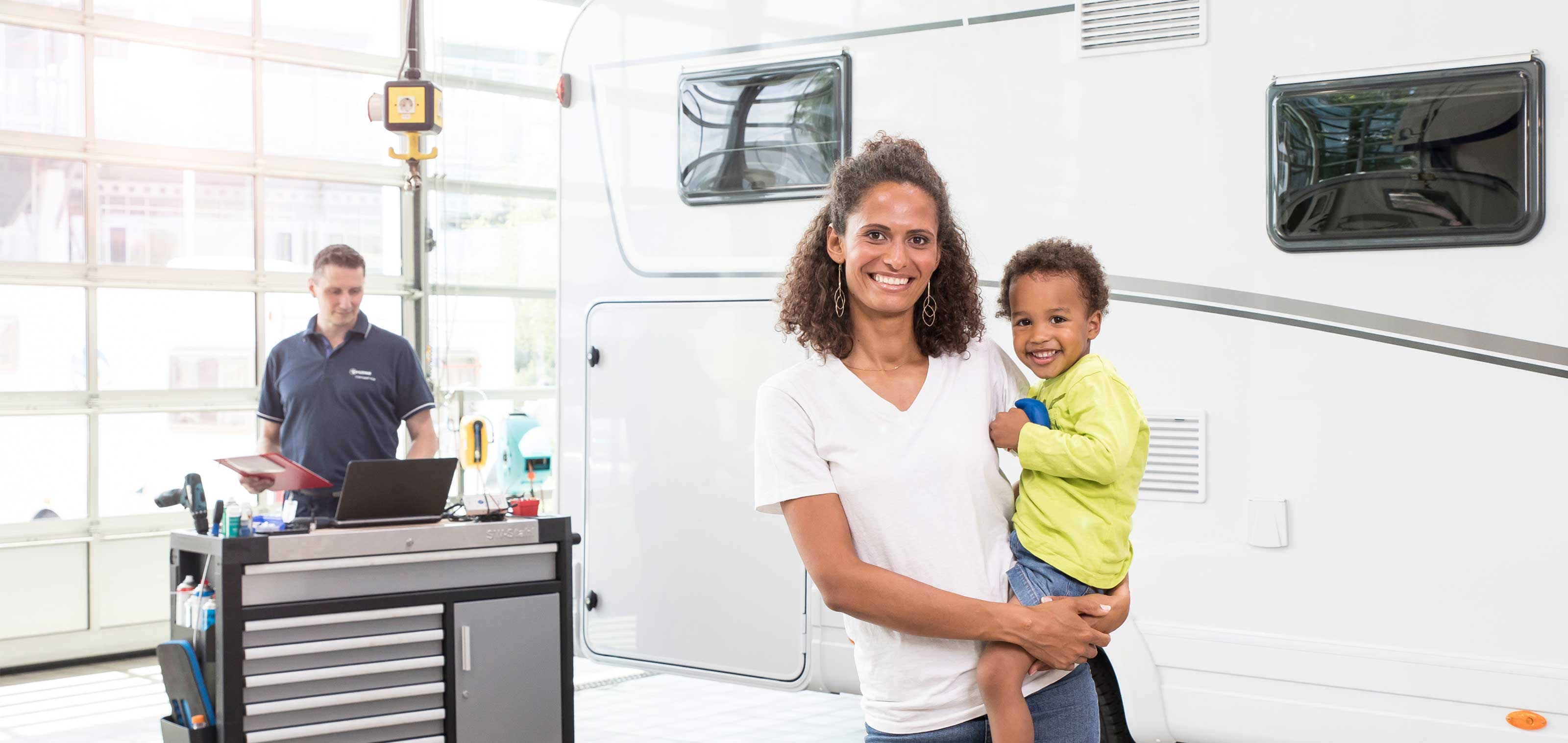 Woman with boy on her arm in front of motor caravan in the Truma service workshop