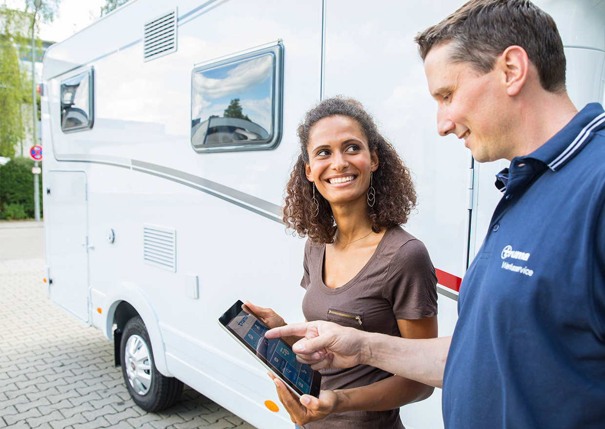 Truma employee showing a tablet with the Truma App to a customer