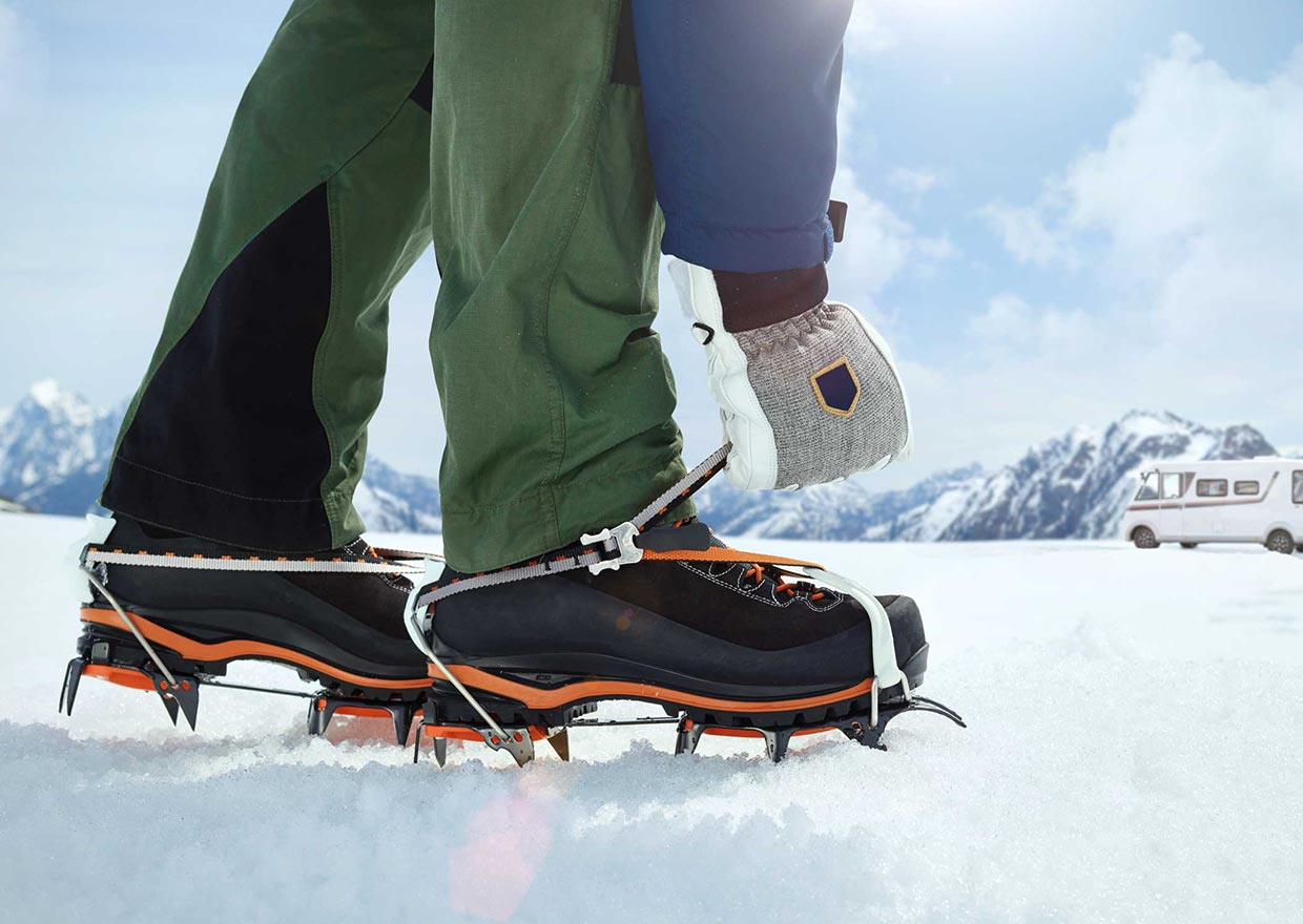 Man with gloves fitting crampons on his shoes in a icy and snowy landscape