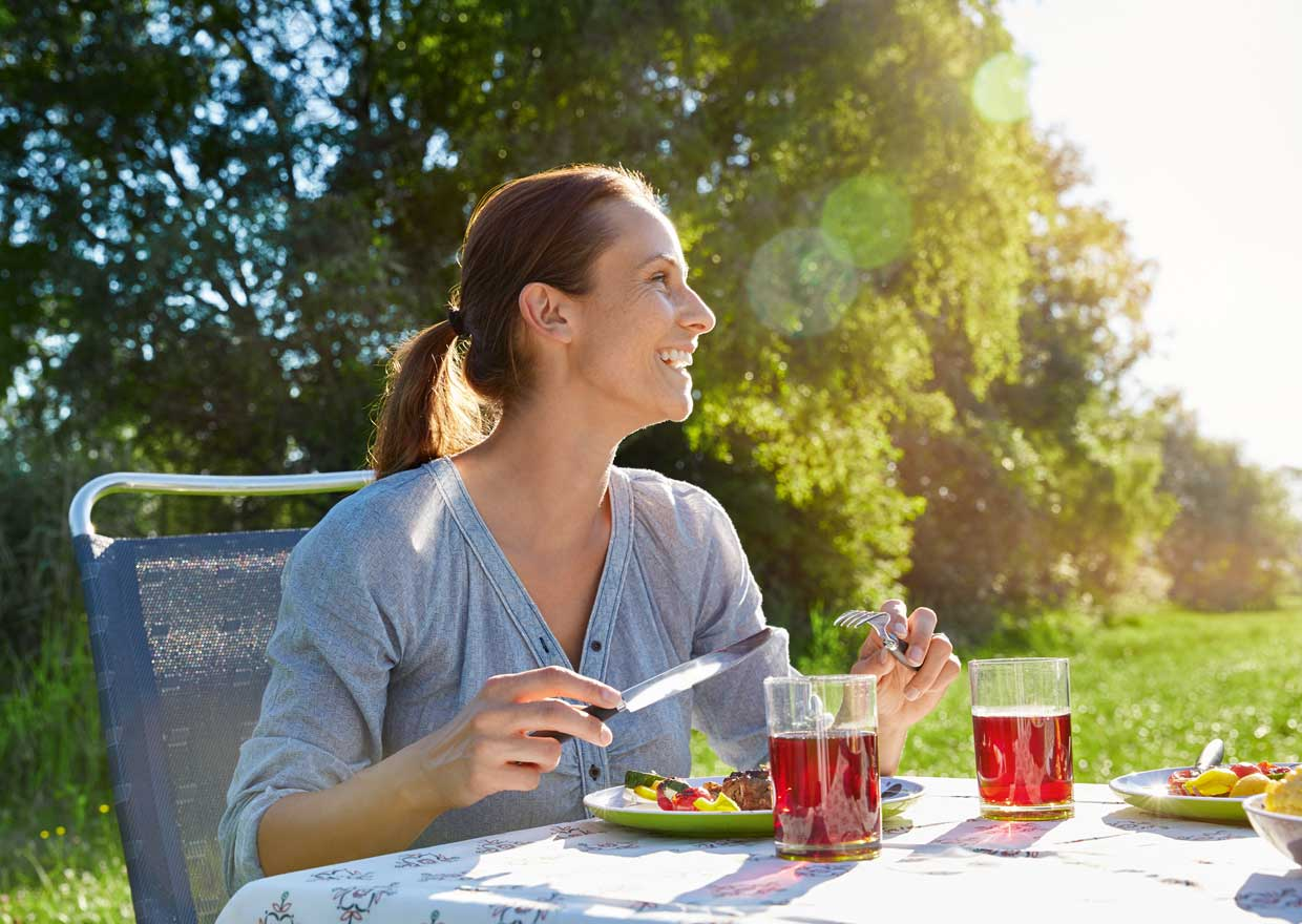 Woman having dinner outdoors in the sun