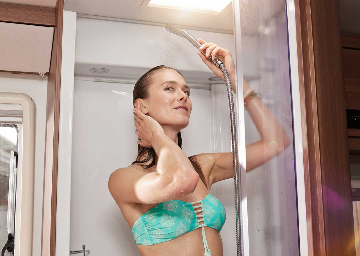 Woman taking a shower in a caravan